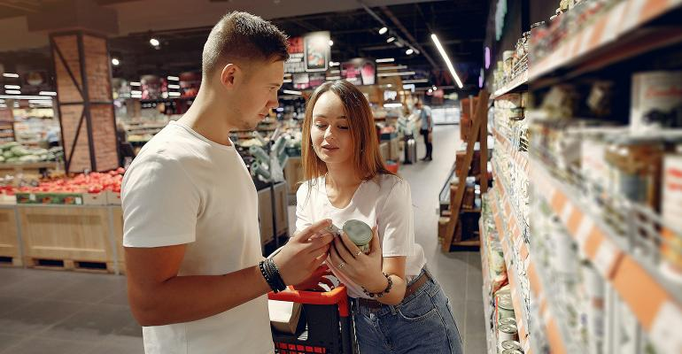 SpoonGuru labeling young couple comparing labels stock image