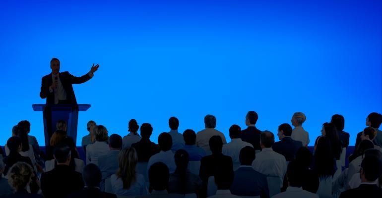 corporate-businessman-giving-presentation-large-audience-freepik-ftd.jpg